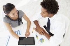 Obenliegende Ansicht der Geschäftsfrau And Businessman Working am Schreibtisch zusammen unter Verwendung Digital-Tablets Stockfoto