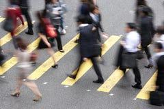 Obenliegende Ansicht der Pendler, die verkehrsreiche Straße kreuzen Stockbild