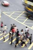 Obenliegende Ansicht der Pendler, die verkehrsreiche Straße kreuzen Stockfotografie