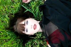 Obenliegende Ansicht der Schönheit liegend im Gras, das Kamera betrachtet lizenzfreie stockfotografie