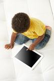 Obenliegende Ansicht des Jungen auf Sofa Playing With Digital Tablet Stockfotografie