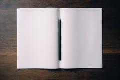 Obenliegende Ansicht des leeren Notizbuches mit schwarzem Bleistift auf hölzernem Tabellen-Hintergrund Stockfoto