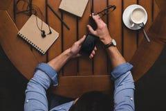obenliegende Ansicht des Mannes, der iphone am Holztisch mit Kaffee verwendet lizenzfreies stockbild