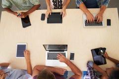 Obenliegende Ansicht des Personals mit Digital-Geräten in der Sitzung Lizenzfreies Stockfoto
