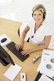 Obenliegende Ansicht des Service-Vertreters Talking To Customer im Call-Center Stockfoto