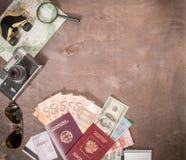 Obenliegende Ansicht Reisender ` s von Zubehör, von Pässen und von Banknoten Reisekonzept auf hölzernem Hintergrund stockfotografie