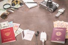 Obenliegende Ansicht Reisender ` s von Zubehör, von Pässen und von Banknoten Reisekonzept auf hölzernem Hintergrund stockbild