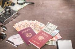 Obenliegende Ansicht Reisender ` s von Zubehör, von Pässen und von Banknoten Reisekonzept auf hölzernem Hintergrund lizenzfreies stockbild
