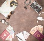 Obenliegende Ansicht Reisender ` s von Zubehör, von Pässen und von Banknoten Reisekonzept auf hölzernem Hintergrund Raum für Text lizenzfreie stockbilder
