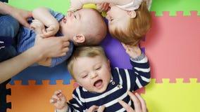 Obenliegende Ansicht von den Babys, die auf Matte an Kindertagesstätte playgroup gekitzelt wird liegen stock video