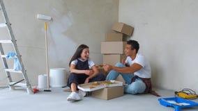 Obenliegende Ansicht von den jungen Paaren, die Pizza beim Sitzen auf Boden in der neuen Wohnung essen stock footage
