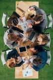 obenliegende Ansicht von den verärgerten Teilhabern, die Diskussion bei Tisch mit Dokumenten und Geräten haben lizenzfreies stockbild
