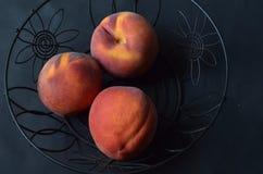 Obenliegende Ansicht von Pfirsichen im schwarzen Drahtkorb Lizenzfreies Stockbild
