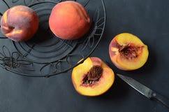 Obenliegende Ansicht von Pfirsichen im schwarzen Drahtkorb, halbierter Pfirsich, Messer Lizenzfreies Stockfoto