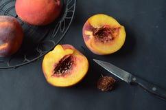 Obenliegende Ansicht von Pfirsichen im schwarzen Drahtkorb, halbierter Pfirsich, Messer Stockfotos