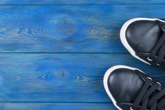 Obenliegende Ansicht von Schuhen auf blauem Bretterboden Schuhe auf einem hölzernen Hintergrund Turnschuhe auf einem Bretterboden Lizenzfreies Stockbild