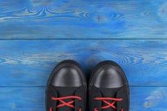 Obenliegende Ansicht von Schuhen auf blauem Bretterboden Schuhe auf einem hölzernen Hintergrund Turnschuhe auf einem Bretterboden Stockfotografie