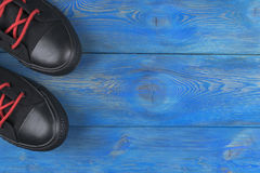 Obenliegende Ansicht von Schuhen auf blauem Bretterboden Schuhe auf einem hölzernen Hintergrund Turnschuhe auf einem Bretterboden Stockbilder