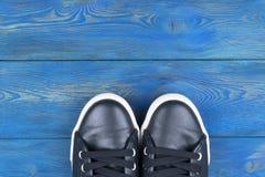 Obenliegende Ansicht von Schuhen auf blauem Bretterboden Schuhe auf einem hölzernen Hintergrund Turnschuhe auf einem Bretterboden Lizenzfreie Stockfotografie