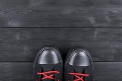 Obenliegende Ansicht von Schuhen auf schwarzem Bretterboden Schuhe auf einem hölzernen Hintergrund Turnschuhe auf einem Bretterbo Lizenzfreies Stockbild