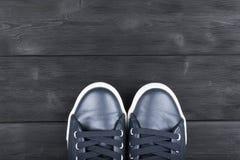 Obenliegende Ansicht von Schuhen auf schwarzem Bretterboden Schuhe auf einem hölzernen Hintergrund Turnschuhe auf einem Bretterbo Lizenzfreie Stockfotos