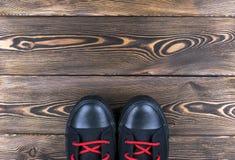 Obenliegende Ansicht von schwarzen Schuhen auf Bretterboden Schuhe auf einem hölzernen Hintergrund Turnschuhe auf einem Bretterbo Lizenzfreies Stockbild