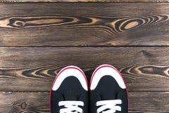 Obenliegende Ansicht von Schwarzweiss-Schuhen auf Bretterboden Schuhe auf einem hölzernen Hintergrund Turnschuhe auf einem Brette Lizenzfreies Stockbild