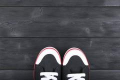 Obenliegende Ansicht von Schwarzweiss-Schuhen auf schwarzem Bretterboden Schuhe auf einem hölzernen Hintergrund Turnschuhe auf ei Lizenzfreies Stockfoto