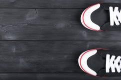Obenliegende Ansicht von Schwarzweiss-Schuhen auf schwarzem Bretterboden Schuhe auf einem hölzernen Hintergrund Turnschuhe auf ei Stockfotografie