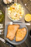 Obenliegende Nehmenleiste panierte Kalbfleisch und kalten Salat; auf Holz lizenzfreie stockfotografie