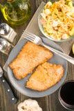 Obenliegende Nehmenleiste panierte Kalbfleisch und kalten Salat; auf Holz lizenzfreie stockfotos