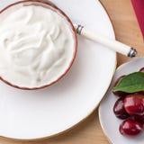 Obenliegende quadratische Ansicht des starken sahnigen natürlichen griechischen Joghurts Stockfotografie