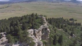 Obenliegende Vogelperspektive der Felsenschluchtwand und des grünen Feldes stock footage
