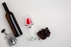 Obenliegende Winkelsicht einer großen Flasche Rotweins, Trinkglas auf weißem Hintergrund lizenzfreie stockfotos
