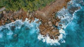 Obenliegender Luftflug des brummens 4k ?ber Granitflusssteinen nahe zu Strand Anse Bazarca Meereswogen, die auf Felsen brechen Ma stock video footage