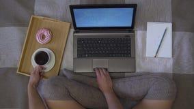 Obenliegender Schuss, ein Mädchen sitzt auf dem Bett und arbeitet unter Verwendung eines Laptops, trinkt Kaffee mit einem Donut stock video
