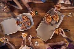 Obenliegender Schuss von Freunden an einem Tisch, der Mitnehmerpizzas teilt lizenzfreie stockfotos