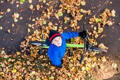 Obenliegendes Foto eines Jungen fährt Fahrrad im Herbstpark Stockfoto