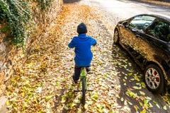Obenliegendes Foto eines Jungen fährt Fahrrad im Herbstpark Stockfotos