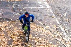 Obenliegendes Foto eines Jungen fährt Fahrrad im Herbstpark Lizenzfreie Stockfotos