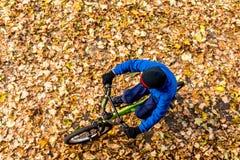 Obenliegendes Foto eines Jungen fährt Fahrrad im Herbstpark Lizenzfreie Stockbilder