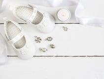 Obenliegendes Foto von Paaren der weißen Babybeuten, Kerze, Band und lizenzfreies stockfoto