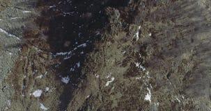 Obenliegendes Luftbrummenflug establisher über schneebedecktem Waldholz Winterschnee in der Gebirgsnatur draußen gerade-unten stock video
