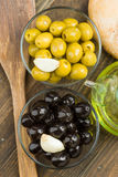 Obenliegendes Nehmen von Oliven, schwarz und grün in der Glasschüssel lizenzfreies stockfoto