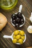Obenliegendes Nehmen von Oliven, schwarz und grün in der Porzellanschüssel lizenzfreie stockfotografie