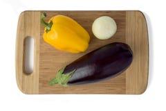 Oberżyna, pieprze i cebule na tnącej desce na białym tle, obraz royalty free