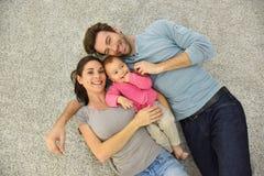 Obere Ansicht der glücklichen jungen Familie auf dem Boden Lizenzfreies Stockfoto
