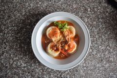 Obere Ansicht von einer Platte von sorrentinos - angefüllte Teigwaren - mit Soße, Parmesankäseparmesankäse und verziert mit den B lizenzfreies stockfoto