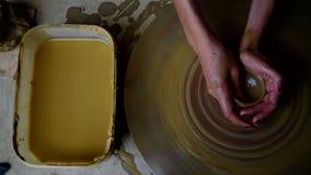 Obere Ansichtfrau stellt kleinen Topf mit gelbem Lehm auf Rad her stock footage