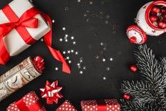 Obere Draufsicht eines roten Bandes, der Weihnachtsgeschenke, der Baumspielwaren und der immergrünen Niederlassung auf einem schw Stockbild